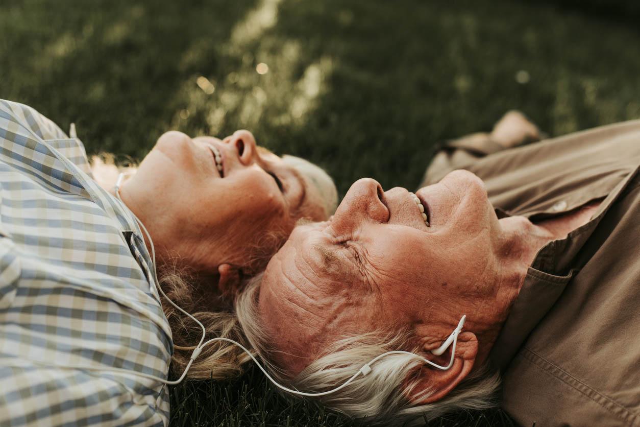 Vue latérale du couple Senior ecoutant de la musique tete contre tete