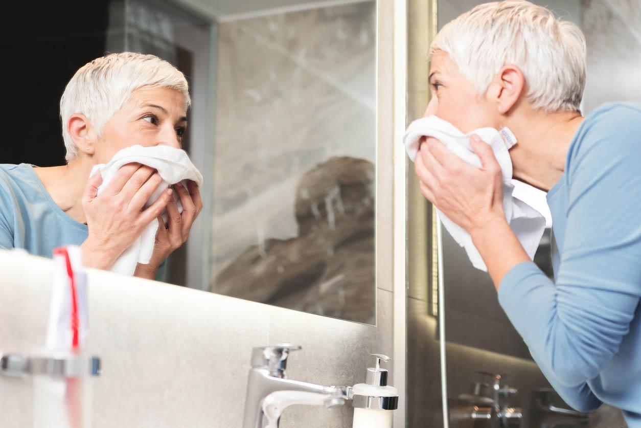 femme senior se demaquille le visage