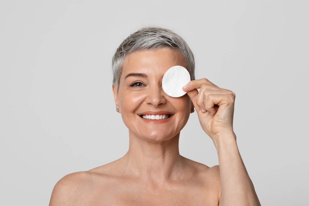femme d'âge moyen couvrant l'oeil avec un coton