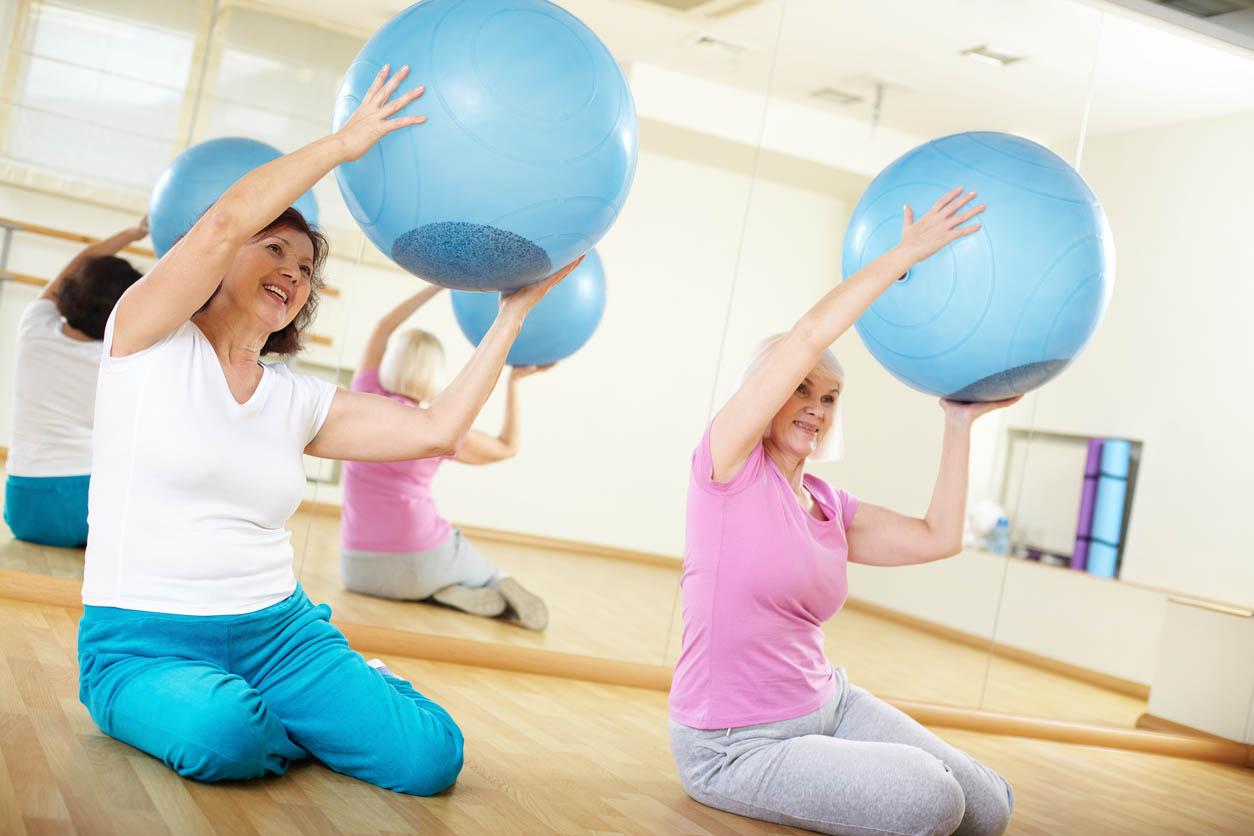 senior faisant des exercices de pilates With Balls
