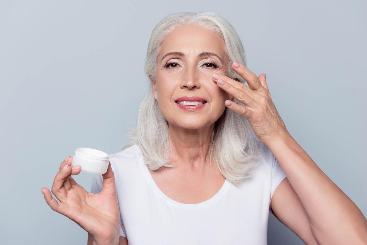 femme applique la crème contour des yeux