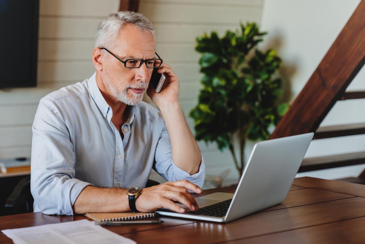 Homme senior travaillant de la maison sur l'ordinateur